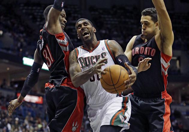 Milwaukee Bucks' O.J. Mayo tries to drive between Toronto Raptors' Terrence Ross (31) and Landry Fields during the second half of an NBA basketball game Saturday, Nov. 2, 2013, in Milwaukee. The Rapto