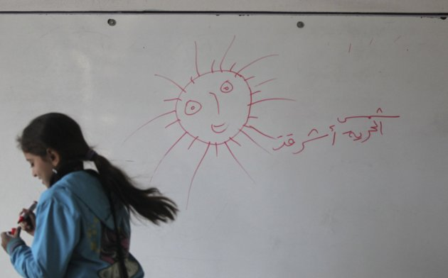 A child writes on a whiteboard at the Oumar Al-Ard Al-Taalimi Education Centre in Masakin Al-Baladiyah, in Aleppo