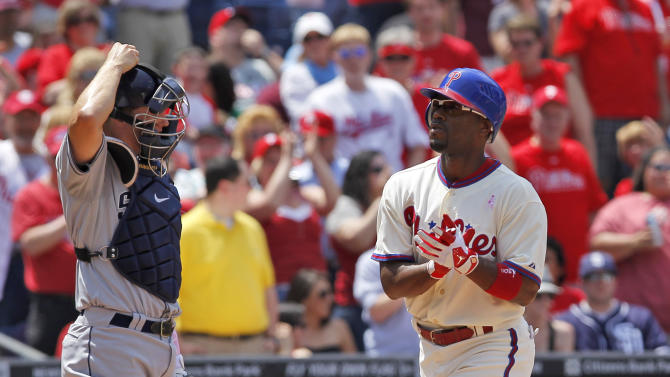 Philadelphia Phillies shortstop Jimmy Rollins (11) reacts as he crosses home next to San Diego Padres catcher Nick Hundley, left, after his solo home run during the first inning of a baseball game Sunday, May 13, 2012, in Philadelphia. (AP Photo/Alex Brandon)