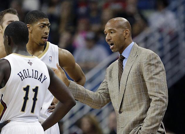 New Orleans Pelicans coach Monty Williams talks to guard Jrue Holiday (11) and forward Anthony Davis in the first half of an NBA basketball game against the Charlotte Bobcats in New Orleans, Saturday,