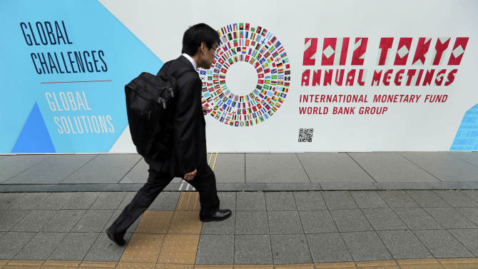 FILE - In this Wednesday, Oct. 10, 2012, file photo, a man walks in front of the venue of the International Monetary Fund and World Bank meeting. When global finance ministers meet this week in Tokyo, they'll confront a triple challenge: Economic troubles in three major regions are threatening the world's economy. (AP Photo/Itsuo Inouye, File)