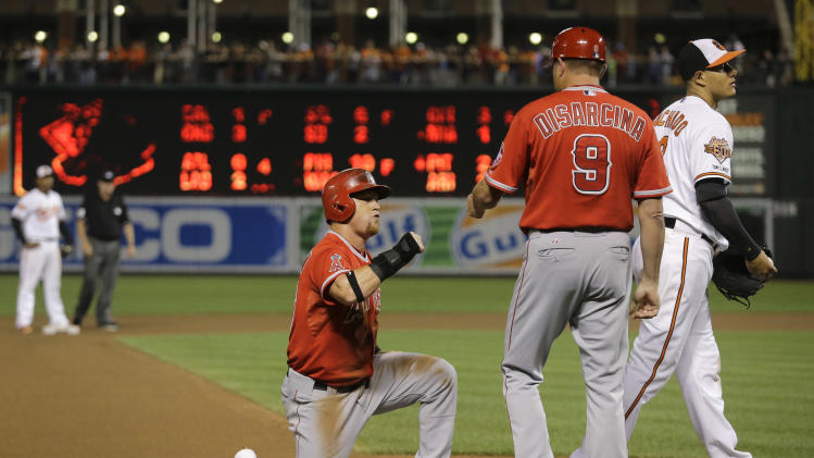 Los Angeles Angels' Kole Calhoun, center, fist-bumps third base coach Gary DiSarcina behind Baltimore Orioles third baseman Manny Machado after reaching third on a single by Mike Trout in the 13th inning of a baseball game, Thursday, July 31, 2014, in Baltimore. Calhoun scored during the next at-bat, and Los Angeles won 1-0. (AP Photo/Patrick Semansky)