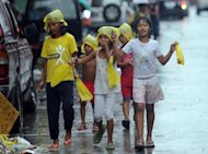 Young survivors of super Typhoon Haiyan brave the rain as they walk the streets to ask for gifts from residents in Tacloban city, Leyte province, on December 25, 2013