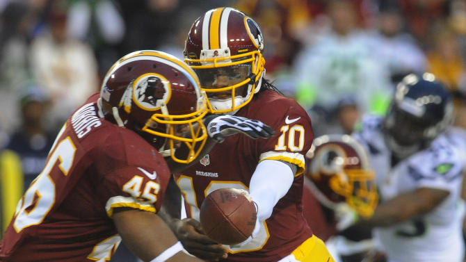 Washington Redskins quarterback Robert Griffin III hands off to running back Alfred Morris during the first half of an NFL wild card playoff football game against the Seattle Seahawks in Landover, Md., Sunday, Jan. 6, 2013. (AP Photo/Richard Lipski)