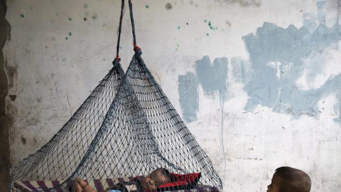 A son of a migrant fisherman from Myanmar rests in a hammock at a former shrimp warehouse where his family lives in Ban Nam Khem