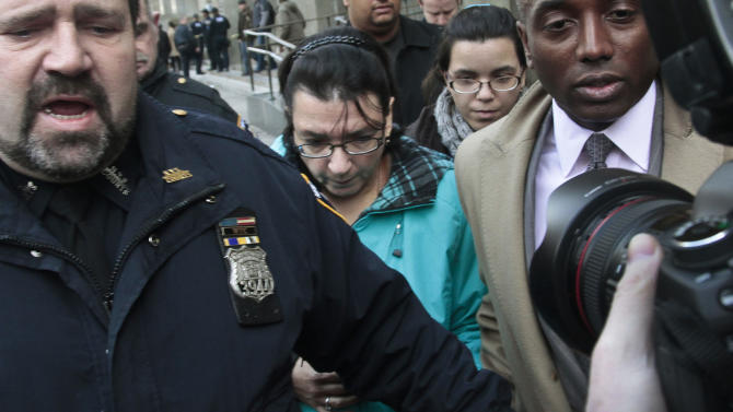 Rosemary Hernandez, center, the wife of Pedro Hernandez, who is charged with killing a New York City boy in 1979, leaves court with their daughter Becky, second from right, Thursday, Nov. 15, 2012 in New York. Pedro Hernandez, who confessed in May to killing 6-year-old Etan Patz, was in court for a brief proceeding and ordered held without bail until his next court date, set for Dec. 12, when he is expected to enter a plea. (AP Photo/Bebeto Matthews)