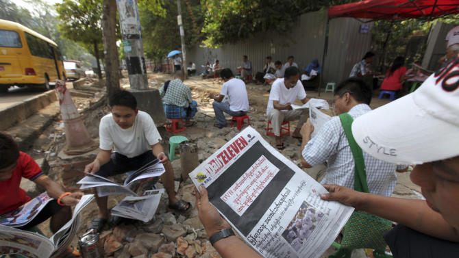 """A man reads a local daily newspaper with its front page printed black with letters saying """"By opposing recent arrest and sentencing of journalists including a video journalist of DVB (Democratic Voice of Burma)"""" with others near a roadside shop Friday, April 11, 2014, in Yangon, Myanmar. Several private newspapers in Myanmar printed black front pages on Friday to protest the recent arrests and sentencing of journalists, in the latest sign the country's media climate is worsening. (AP Photo/Khin Maung Win)"""