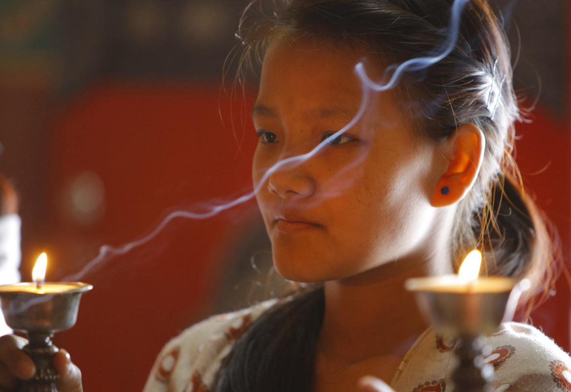 Sumi Sherpa lights a butter lamp during one-year death anniversary rituals for her father Ang Kaji Sherpa, a victim of last year's deadly avalanche in Everest, at a monastery in Kathmandu, Nepal, Saturday, April 18, 2015. April 18 marks the first year anniversary of an ice avalanche that killed 16 guides in the mountain's deadliest disaster. (AP Photo/Niranjan Shrestha)
