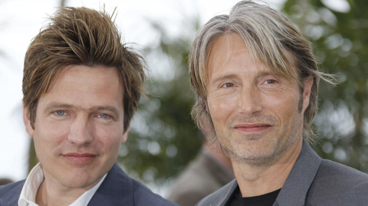 """FILE - This is a Sunday, May 20, 2012 file photo of Director Thomas Vinterberg, left, and actor Mads Mikkelsen pose during a photo call for The Hunt at the 65th international film festival, in Cannes, southern France. When Danish director Thomas Vinterberg wrote the script for """"The Hunt"""" _one of this year's contenders for Best Foreign Language Film _ he pictured a young Robert de Niro as the lonely teacher in his 40s whose life crumbles because of an innocent lie. And he reached out to Mads Mikkelsen. """"It was really awesome when I got Mads,"""" he said. """"But, I had to rewrite the script."""" (AP Photo/Joel Ryan, File)"""