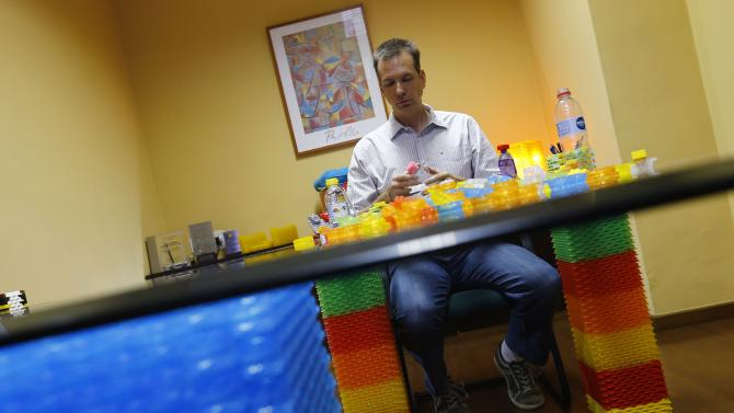 Brazilian inventor Vollers sits on a table with legs handmade with bottle caps, in Rio de Janeiro