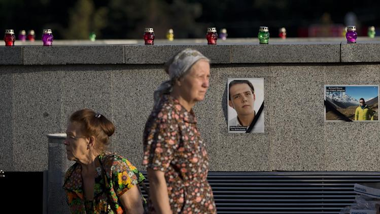 A woman is backdropped by pictures of victims of the MH17 air crash during a memorial concert in Kharkiv, Ukraine, Thursday, July 24, 2014. Two military aircraft carrying remains of victims from the Malaysian plane disaster departed for the Netherlands on July 24, while Australian and Dutch diplomats joined to promote a plan for a U.N. team to secure the crash scene which has been controlled by pro-Russian rebels.(AP Photo/Vadim Ghirda)