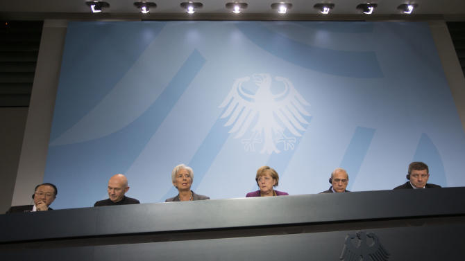 World Bank president Jim Yong Kim, World Trade Organization Director General Pascal Lamy, Christine Lagarde Managing Director of the International Monetary Fund, German Chancellor Angela Merkel, OECD General Secretary Angel Gurria and Chairman of the International Labour Organization Guy Ryder, from left, brief the media after a meeting at the chancellery in Berlin, Tuesday, Oct. 30, 2012. (AP Photo/Markus Schreiber)
