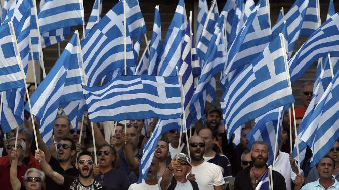 Supporters and members of extreme-right Golden Dawn party wave Greek national flags and shout slogans outside the Greek police headquarters in Athens