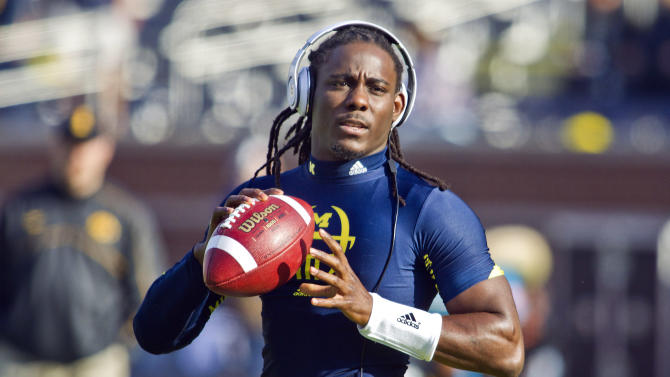 Michigan quarterback Denard Robinson warms up by throwing passes before an NCAA college football game against Iowa, Saturday, Nov. 17, 2012, in Ann Arbor, Mich. Robinson has missed the past two games with nerve damage in his elbow. (AP Photo/Tony Ding)