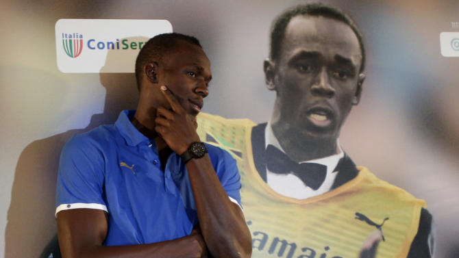 Olympic and world 100-meter record holder Usain Bolt, of Jamaica, poses next to a giant photograph of himself during a press conference in a Rome hotel, Tuesday, May 24, 2011. Bolt will make his season debut in Thursday's Golden Gala meet in Rome, his first race since getting beat by Tyson Gay in Stockholm last August to end his two-year unbeaten streak. (AP Photo/Pier Paolo Cito)