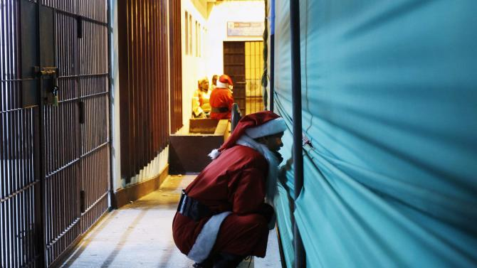 An inmate dressed as Santa Claus watches on backstage an event ahead of Christmas celebrations at Santa Monica female prison in Lima