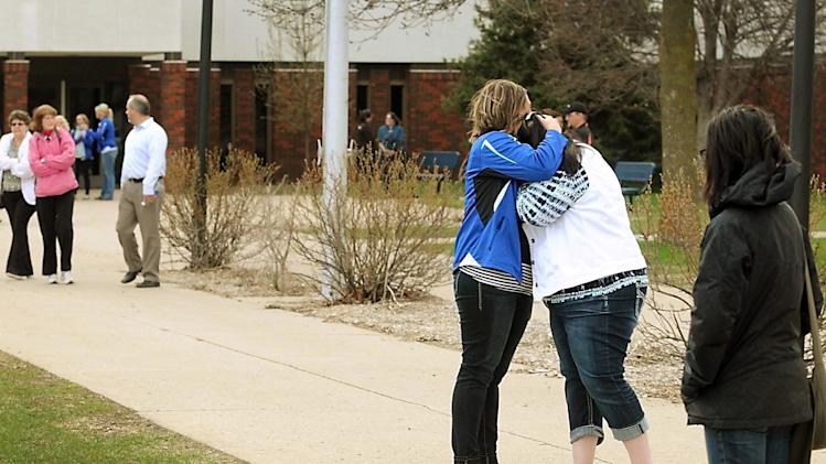 FILE - In this May 2, 2014, file photo two women hug after leaving a community meeting on school safety at the Waseca Junior and Senior High School after a teenager accused of planning to massacre his family and high school classmates in Waseca, Minn. On Monday, July 28, 2014 a judge has dismissed the most serious charges against a 17-year-old boy accused of plotting to kill his family and attack his southern Minnesota school. (AP Photo/Mankato Free Press, Pat Christman, File)