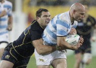 Argentina's Felipe Contepomi holds onto the ball as he is tackled by Scotland's Sean Lamont during their Rugby World Cup Pool B match at the Wellington Regional stadium, New Zealand, Sunday, Sept. 25, 2011. (AP Photo/Natacha Pisarenko)