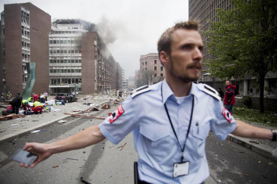 An official attempts to clear away spectators from buildings in the center of Oslo, Friday July 22, 2011, following an explosion that tore open several buildings including the prime minister's office, shattering windows and covering the street with documents. (AP Photo/Fartein Rudjord)  NORWAY OUT