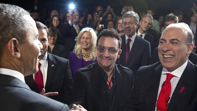 President Barack Obama greets U2 front man Bono, center, and Muhtar Kent the chairman of the Board and chief executive officer of The Coca-Cola Company, right, after speaking during a World AIDS Day event at George Washington University in Washington, Thursday, Dec. 1, 2011n. (AP Photo/Carolyn Kaster)