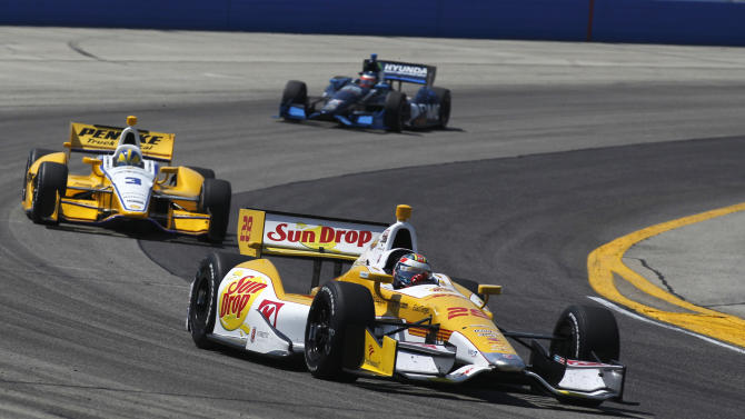Ryan Hunter-Reay (28) and Helio Castroneves (3), of Brazil, drive through a turn during the IndyCar auto race at the Milwaukee Mile in West Allis, Wis., Saturday, June 16, 2012. (AP Photo/Jeffrey Phelps)