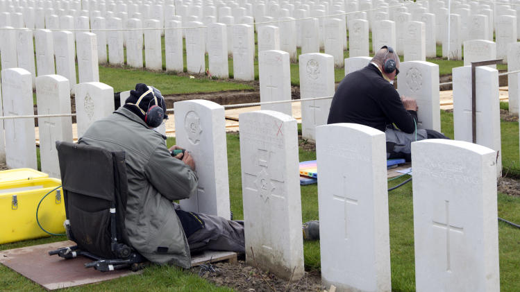 Two engravers work on re-engraving the headstones of WWI soldiers at Tyne Cot cemetery in Zonnebeke, Belgium on Monday, April 15, 2013. With nearly 12,000 graves the cemetery is the largest Commonwealth war cemetery in the world in terms of burials. Commonwealth cemeteries around the world are currently being renovated in preparation for centenary events which begin in 2014. (AP Photo/Virginia Mayo)