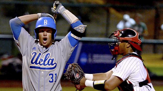 UCLA's Darrell Miller Jr. is tagged out on a dropped third strike by Maryland's Kevin Martir for the last out of the ninth inning during the NCAA college baseball tournament regional game in Los Angeles on Monday, June 1, 2015. Maryland won 2-1. (AP Photo/Jayne Kamin-Oncea)