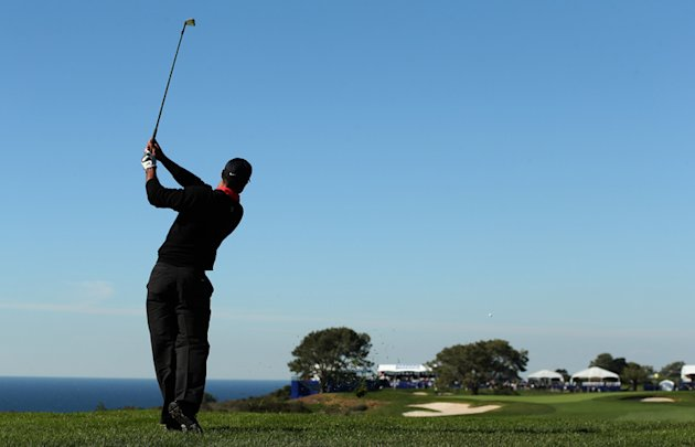 Tiger Woods hits his second shot on the 14th hole during the final round of the Farmers Insurance Open on the South Course at Torrey Pines Golf Course on January 28, 2013 in La Jolla, California. Phot