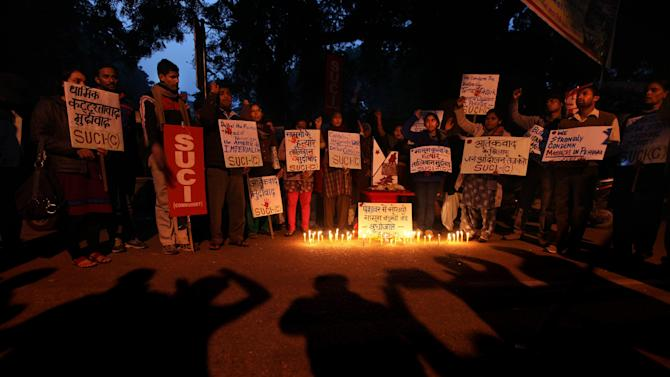 """Activists of Socialist Unity Centre of India (Communist) or SUCI(C) hold placards and shout slogans against Tuesday's Taliban attack on a military-run school in Peshawar, during a candlelight vigil in New Delhi, India, Thursday, Dec. 18, 2014. The Pakistani government and military vowed a stepped up campaign aimed at rooting out militant strongholds in the country's tribal regions along the border with Afghanistan after a Taliban massacre that killed more than 140 people, mostly children, on a military-run school. The placards read, left, """"Down with Religious Extremism"""", fourth left, """"Down with Taliban - Killers of Innocent Children"""", second right, """"Raise Voice Against Terrorism"""". (AP Photo/Altaf Qadri)"""