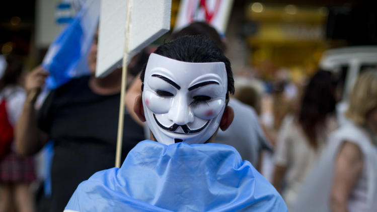 A protester wearing a mask on the back of his head and an Argentine flag marches during anti government demonstration in Buenos Aires, Argentina, Thursday, Nov. 8, 2012. Thousands of people marched against rising inflation, crime, exchange controls and to express their fear to a constitutional reform that could open the way for a third consecutive reelection of Argentina's President Cristina Fernandez. (AP Photo/Victor R. Caivano)