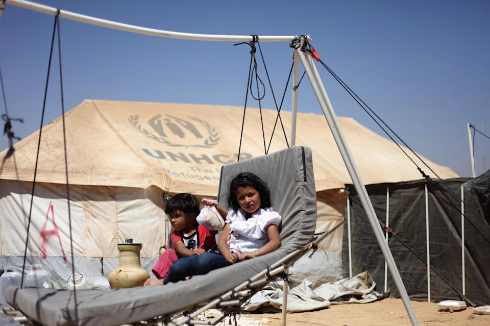 Syrian refugee children sit on a handmade swing in front of their tent, at Zaatari Refugee Camp, in Mafraq, Jordan, Sunday, Sept. 2, 2012.  (AP photo/Mohammad Hannon)