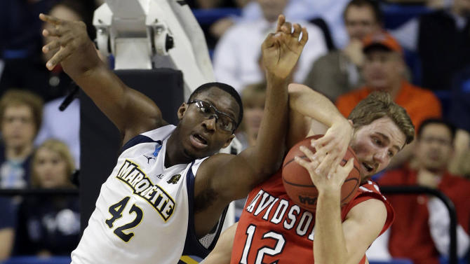 Marquette guard Derrick Wilson (12) and Davidson guard Nik Cochran (12) fight for a rebound during the first half of their second-round game in the NCAA college basketball tournament, Thursday, March 21, 2013, in Lexington, Ky. Butler won  68-56. (AP Photo/John Bazemore)