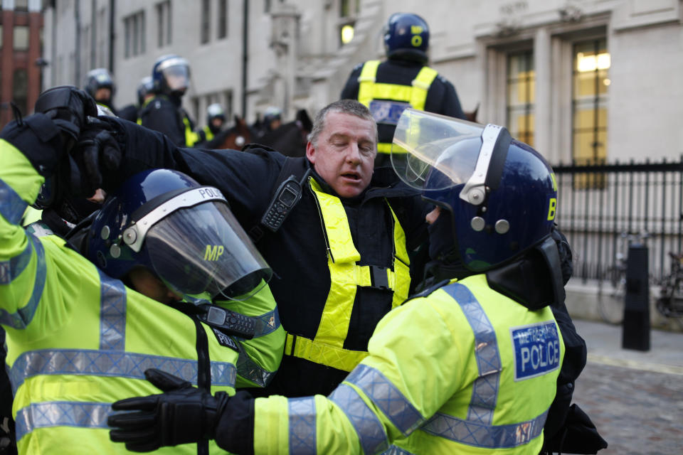 Police officers carry an injured officer during a protest against an increase in tuition fees on the edge of Parliament Square in London, Thursday, Dec. 9, 2010.  Police clashed with protesters marching to London's Parliament Square as lawmakers debated a controversial plan to triple university tuition fees in England.(AP Photo/Karel Prinsloo)