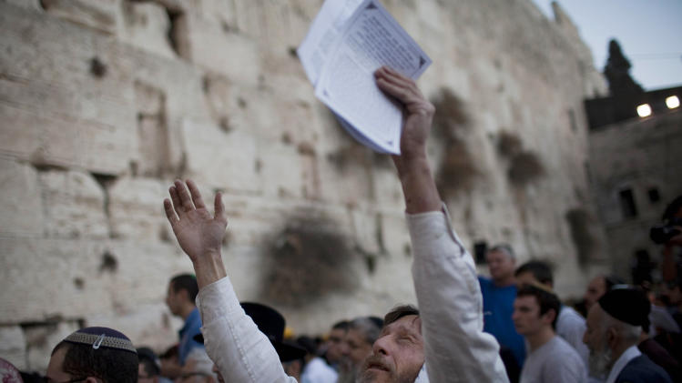 FILE - In this Nov. 29, 2010 file photo, a Jewish man raises his hands as he and others pray for rain at the Western Wall, the holiest site where Jews can pray, in Jerusalem's Old City. The Palestinian government has removed a report claiming that Jerusalem's Western Wall isn't holy to Jews from an official website Wednesday after it provoked furious reaction. (AP Photo/Bernat Armangue, Files)