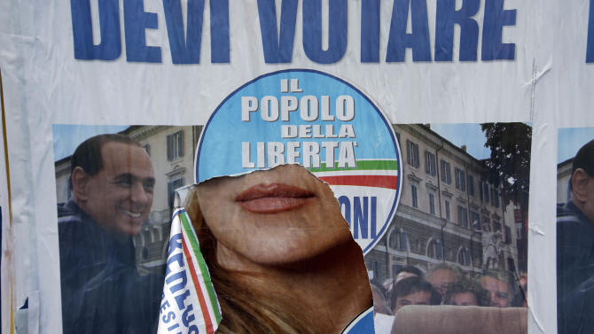 A torn electoral poster shows center-right coalition leader Silvio Berlusconi in Rome, Monday, Feb. 25, 2013. Italy's crucial elections appear to be heading toward gridlock, initial results show, with the center-left forces of Pier Luigi Bersani headed toward victory in the lower house of Parliament and the camp of former premier Silvio Berlusconi gaining the upper hand in the equally powerful Senate. The upstart protest campaign of comic-turned-politician Beppe Grillo was also showing a stunningly strong result in both houses of the legislature, confirming its surprise role as a force in Italian politics. (AP Photo/Gregorio Borgia)