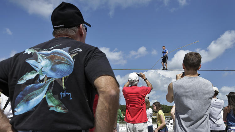 Spectators watch as high wire performer Nik Wallenda walks across a wire as he practices Tuesday, June 18, 2013 in Sarasota, Fla. Wallenda, a seventh generation high-wire walker, will attempt to walk across the Grand Canyon on Sunday, June 23, 2013. (AP Photo/Chris O'Meara)