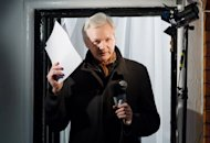 Wikileaks founder Julian Assange addresses media from the window of the Ecuadorian embassy in London, on December 20, 2012. Assange on Friday urged US officials to leak secret documents on drone strikes, saying that the broad discretion to kill citizens showed a &quot;collapse&quot; in the American system
