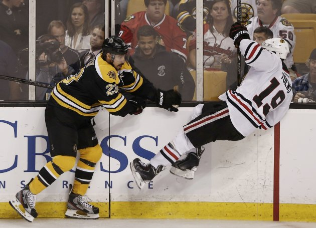 Bruins' Kelly checks Blackhawks' Toews during the second period in Game 4 of their NHL Stanley Cup Finals hockey series in Boston