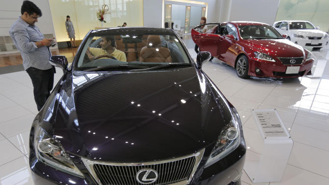 "Visitors look at ""Lexus"" IS350C displayed at a Toyota's showroom in Tokyo, Friday, Aug. 3, 2012.  Toyota says April-June profit zoomed to 290.3 billion yen ($3.7 billion) from 1.1 billion yen on a jump in global sales as the Japanese automaker makes a comeback from a disaster plagued 2011. (AP Photo/Itsuo Inouye)"