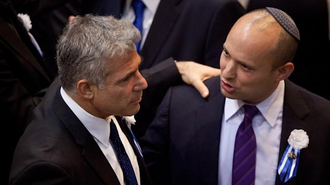 Yair Lapid, leader of the Yesh Atid (There is a Future) party, left, and Naftali Bennett, head of Israel's Jewish Home party, talk during the opening session of Israel's newly elected parliament in Jerusalem, Tuesday, Feb. 5, 2013. Israel's president praised President Barack Obama's approach to countering Iran's suspect nuclear program on Tuesday, while sending a veiled message to Israel's incoming government not to act alone to stop it. (AP Photo/Uriel Sinai, Pool)