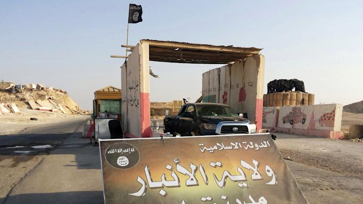 "In this Tuesday, July 22, 2014 photo, a sign is posted at a checkpoint belonging to the Islamic State group, captured from the Iraqi Army, at the main entrance of Rawah, 175 miles (281 kilometers) northwest of Baghdad, Iraq. Arabic reads,""Islamic State, the Emirate of Anbar, City of Rawah."" It has been nearly six weeks since a Sunni militant blitz led by the Islamic State extremist group seized large swaths of northern and western Iraq. (AP Photo) (AP Photo)"