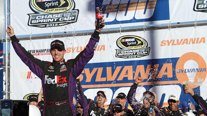 NASCAR driver Denny Hamlin celebrates with his team after winning the NASCAR Sprint Cup Series auto race at New Hampshire Motor Speedway, Sunday, Sept. 23, 2012, in Loudon, N.H. (AP Photo/Jim Cole)