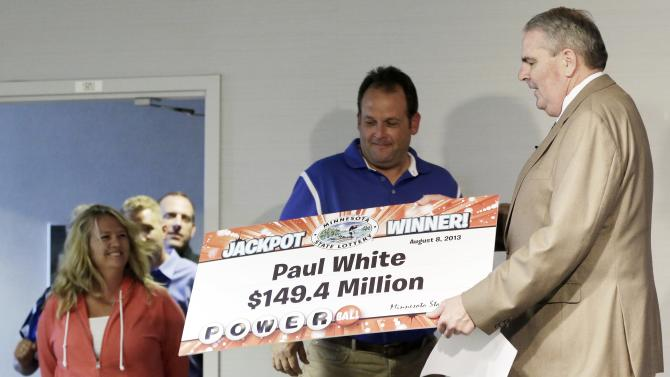 Paul White, of Ham Lake, Minn. holds up a sign showing his winning share during a presentation from Minnesota Lottery executive director Ed Van Petten, right, during a news conference after White was announced one of the winners of the $448.4 million Powerball Jackpot, Thursday, Aug. 8, 2013 in Minneapolis. White's share of the jackpot is $149.4 million. At rear left is White's girlfriend, Kim VanReese. (AP Photo/Jim Mone)