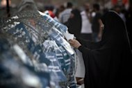 A Bahraini Shiite Muslim woman attaches a pro-democracy flyer to a barbed wire around a police station during an anti-government rally in the village of Shakhora, west of Manama, on September 14. The Shiite-led opposition&#39;s demands for an elected government involve constitutional changes that would reduce the power of the ruling dynasty