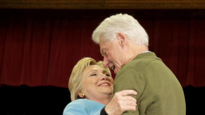 Democratic U.S. presidential candidate Hillary Clinton is embraced by her husband former President Bill Clinton at a campaign event at Alverine High School in Hudson
