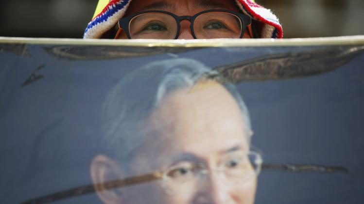 An anti-government protester holds picture of Thailand's King Bhumibol Adulyadej as she joins others following King's birthday address to nation broadcasted on a screen in Bangkok