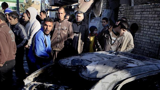 Neighbors react at the scene of a car bomb attack in Hurriya neighborhood of Baghdad, Iraq, Thursday, Jan. 10, 2013. A car bomb explosion near a bus stop in the capital, have killed and wounded scores of people, police said. (AP Photo/Karim Kadim)