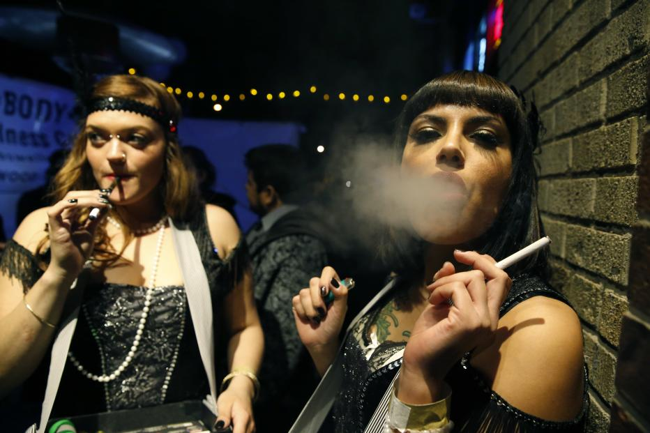 Partygoers smoke marijuana, left, and cigarettes during a Prohibition-era themed New Year's Eve party celebrating the start of retail pot sales, at a bar in Denver, late Tuesday Dec. 31, 2013. Colorado is to begin marijuana retail sales on Jan. 1, a day some are calling 'Green Wednesday.' (AP Photo/Brennan Linsley)