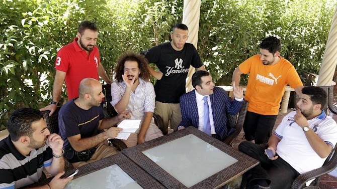 "Iraqi Ahmad al-Basheer (3rdR), host of the ""Basheer Show"", poses with his team on July 29, 2015 at his studio in the Jordanian capital, Amman"