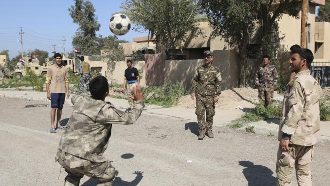 Iraqi security forces and Shi'ite fighters play soccer at Udhaim dam, north of Baghdad